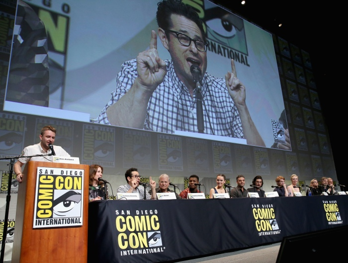 """SAN DIEGO, CA - JULY 10:  (L-R) Moderator Chris Hardwick, producer Kathleen Kennedy, director J.J. Abrams, screenwriter Lawrence Kasdan and actors John Boyega, Daisy Ridley, Oscar Isaac, Adam Driver, Domhnall Gleeson, Gwendoline Christie, Carrie Fisher, Mark Hamill and Harrison Ford at the Hall H Panel for """"Star Wars: The Force Awakens"""" during Comic-Con International 2015 at the San Diego Convention Center on July 10, 2015 in San Diego, California.  (Photo by Jesse Grant/Getty Images for Disney) *** Local Caption *** Chris Hardwick; Kathleen Kennedy; J.J. Abrams; Lawrence Kasdan; John Boyega; Daisy Ridley; Oscar Isaac; Adam Driver; Domhnall Gleeson; Gwendoline Christie; Carrie Fisher; Mark Hamill; Harrison Ford"""